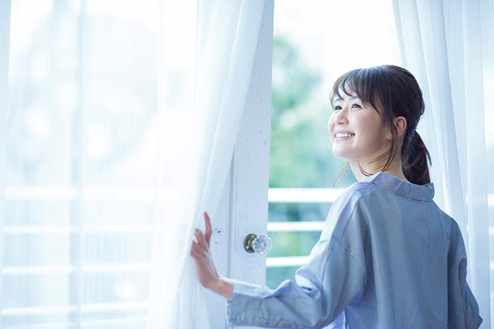 窓の外を眺める笑顔の素敵な女性