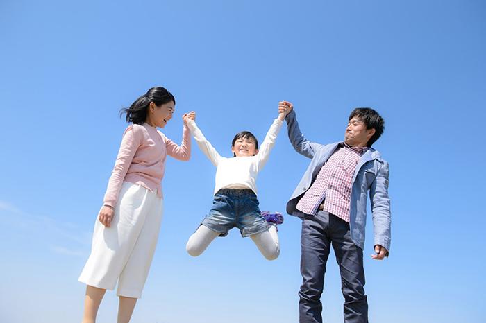 手をつなぎ笑顔の子供と親